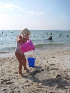 Girl pouring water onto the beach from a bucket