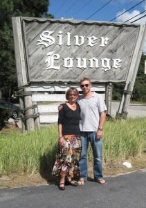 Two people in front of the sign for The Silver Lodge, North Falmouth, Massachusetts