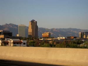 Downtown Tucson with highway guardrail in foreground and Santa Catalina mountains in background