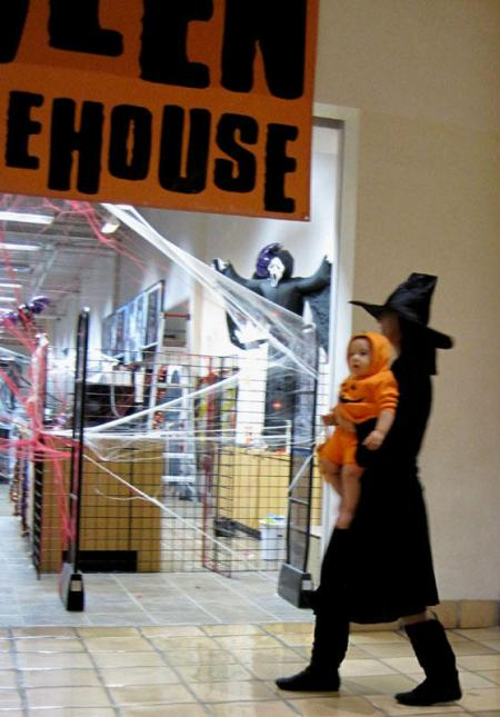 Witch and pumpkin entering a store