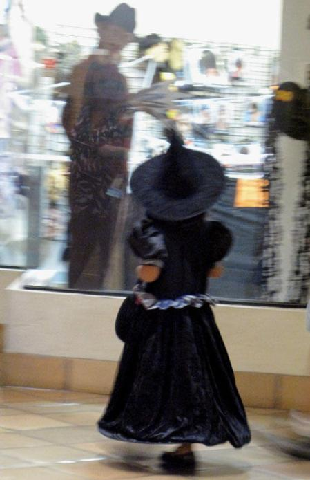 Girl in witch costume looking at mannikin in store window