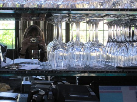 Sparkling wine glasses in a bar with the photographer in the background.