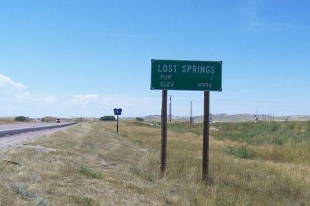 Green road sign of Lost Springs with POP 1