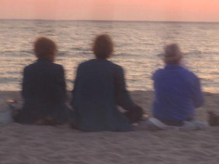 Three women sitting at the beach watching sunset
