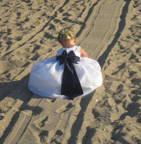 Little Flower Girl playing in the beach sand