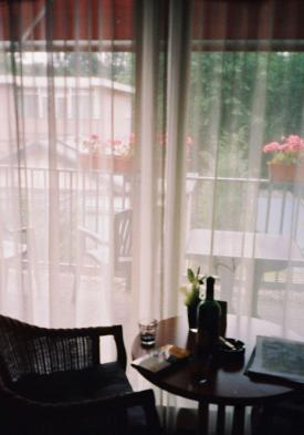 A table with bottle of wine next to the window decorated with delicate curtains