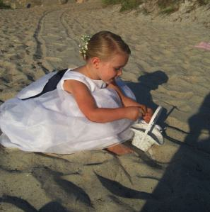 Flower Girl smiling while playing with the sand